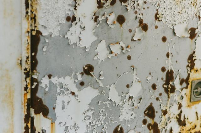 塗装が錆て剥がれ落ちたドアの写真