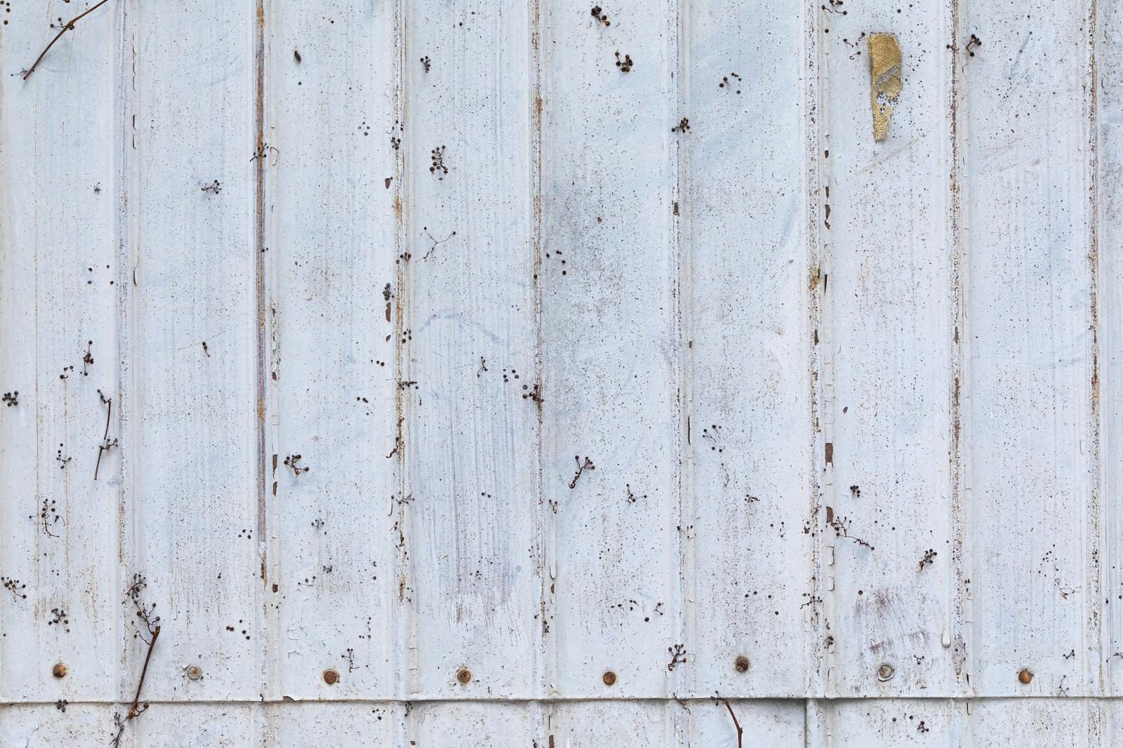 「錆びてペンキを上塗りしたトタンの壁」の写真