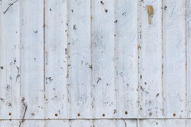 錆びてペンキを上塗りしたトタンの壁の写真