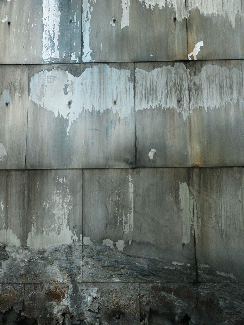 「下部が崩れかけるコンクリートの壁(テクスチャ)」の写真