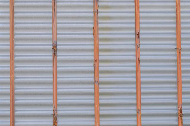 鉄棒で支えるフェンス裏側の写真