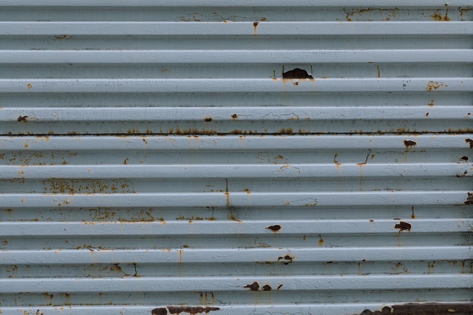 「錆びた凹凸のあるフェンス」の写真