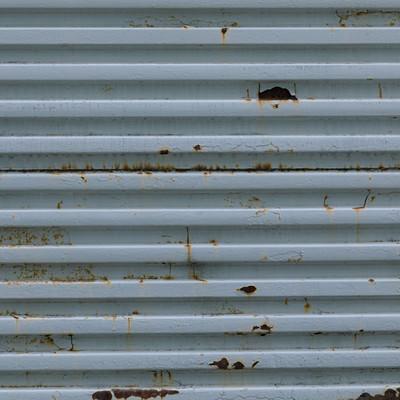 錆びた凹凸のあるフェンスの写真