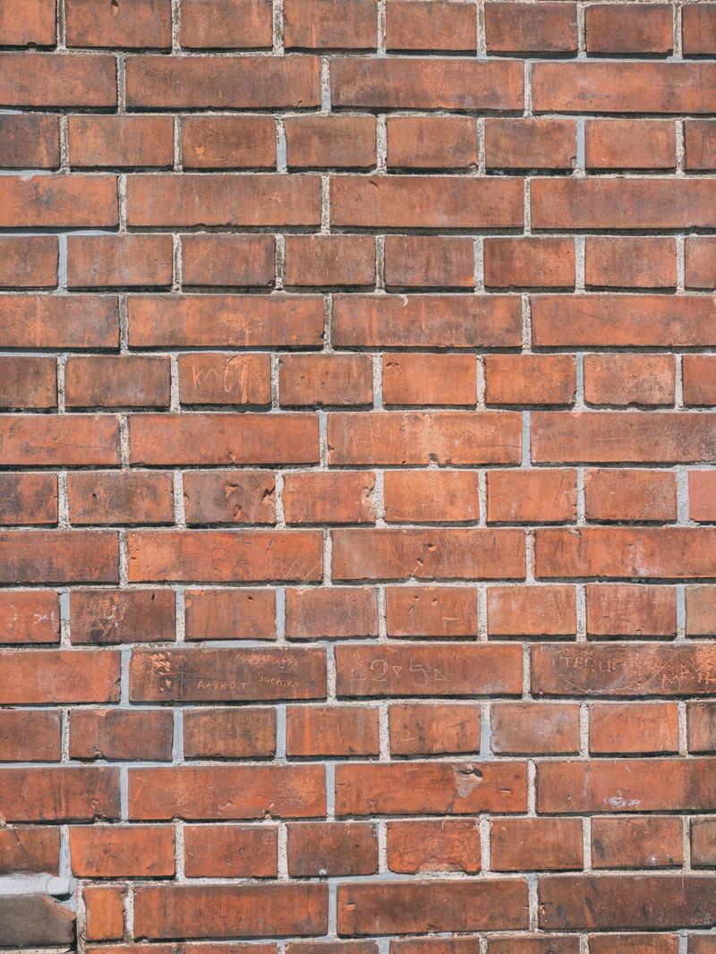 「赤レンガの壁と落書き(テクスチャー)」の写真