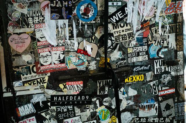 ステッカーが貼られまくっている壁の写真