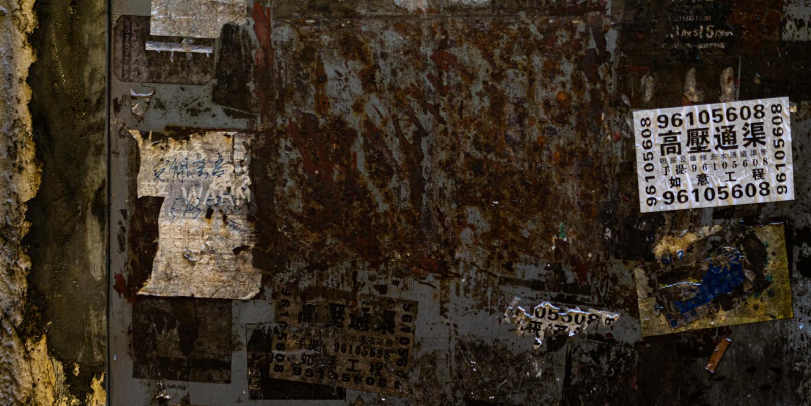 「錆びついて腐食した扉と貼られたチラシ」の写真
