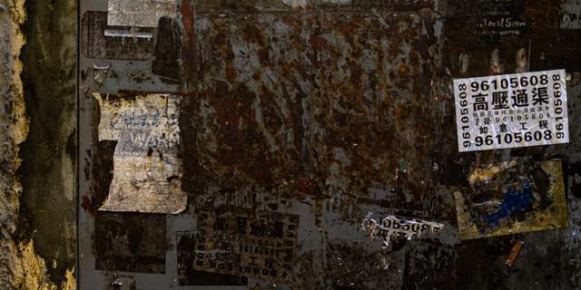 錆びついて腐食した扉と貼られたチラシの写真