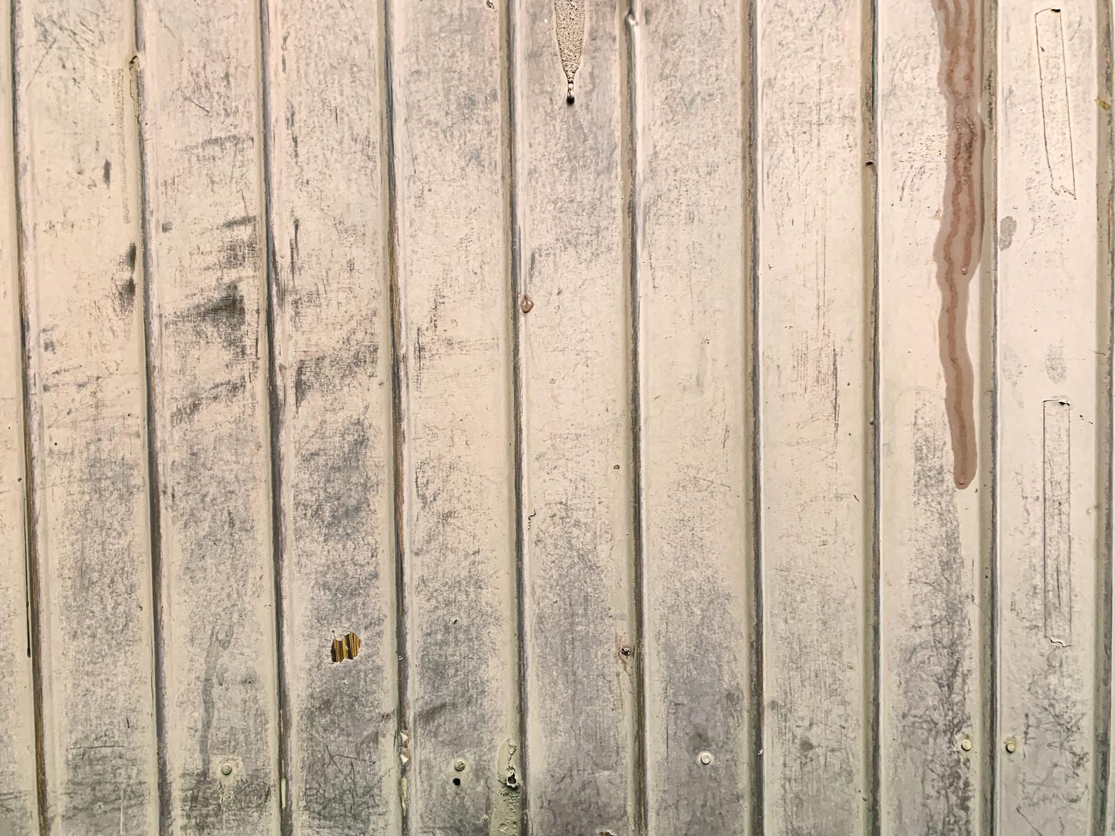 「風化によりペンキが褪せた壁」の写真