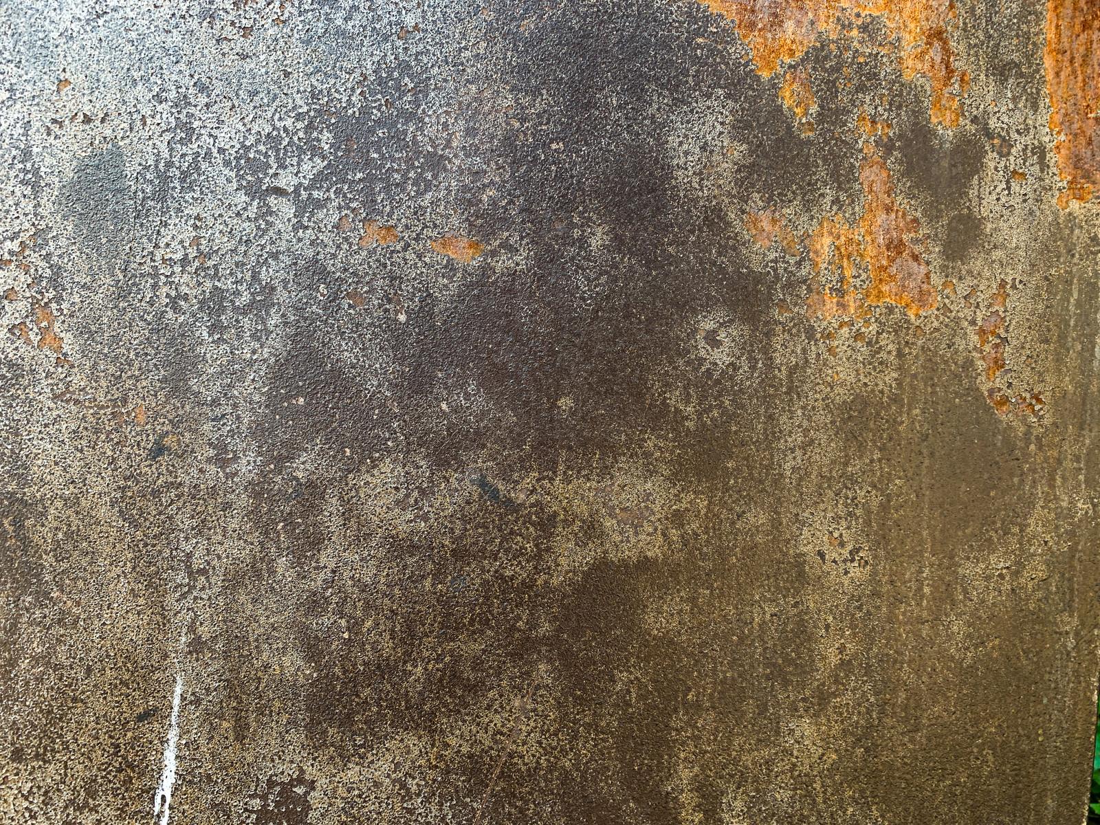 「剥がれた部分が錆び付いた鉄壁(テクスチャ)」の写真