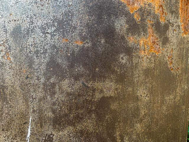 剥がれた部分が錆び付いた鉄壁(テクスチャ)の写真