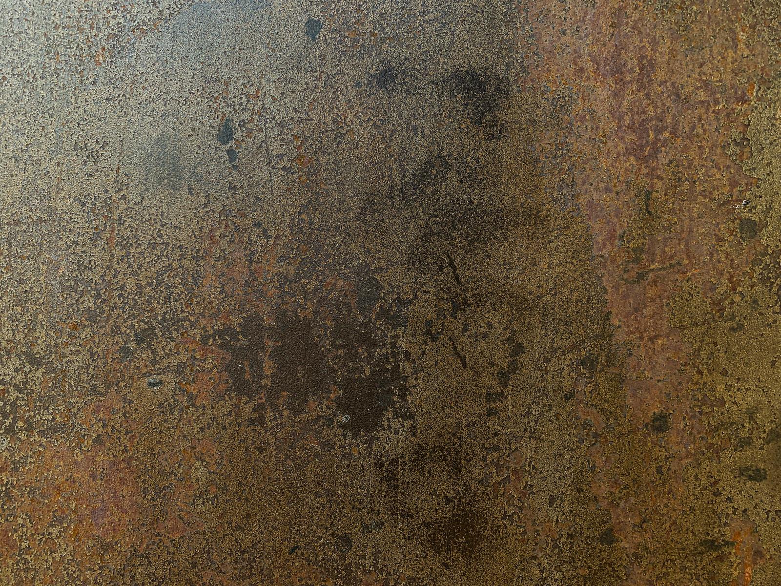 「剥がれ落ちた表面を錆と汚れが染み付く鉄壁(テクスチャ)」の写真