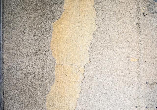 塗装が剥げ落ちる壁の写真