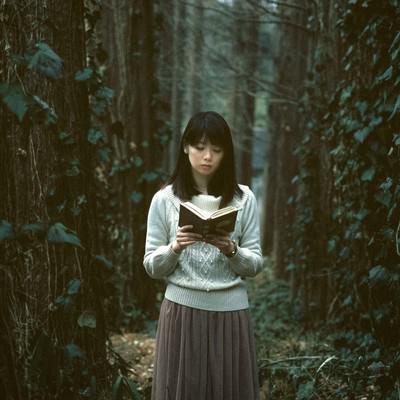 「深い森に迷い込んだ読書美女」の写真素材