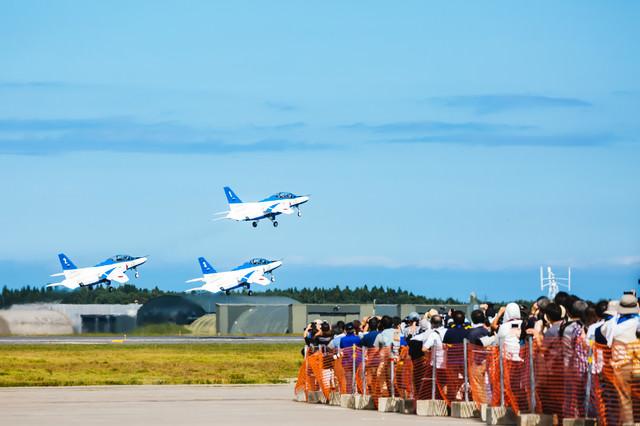 飛び立つブルーインパルス3機と観客の写真