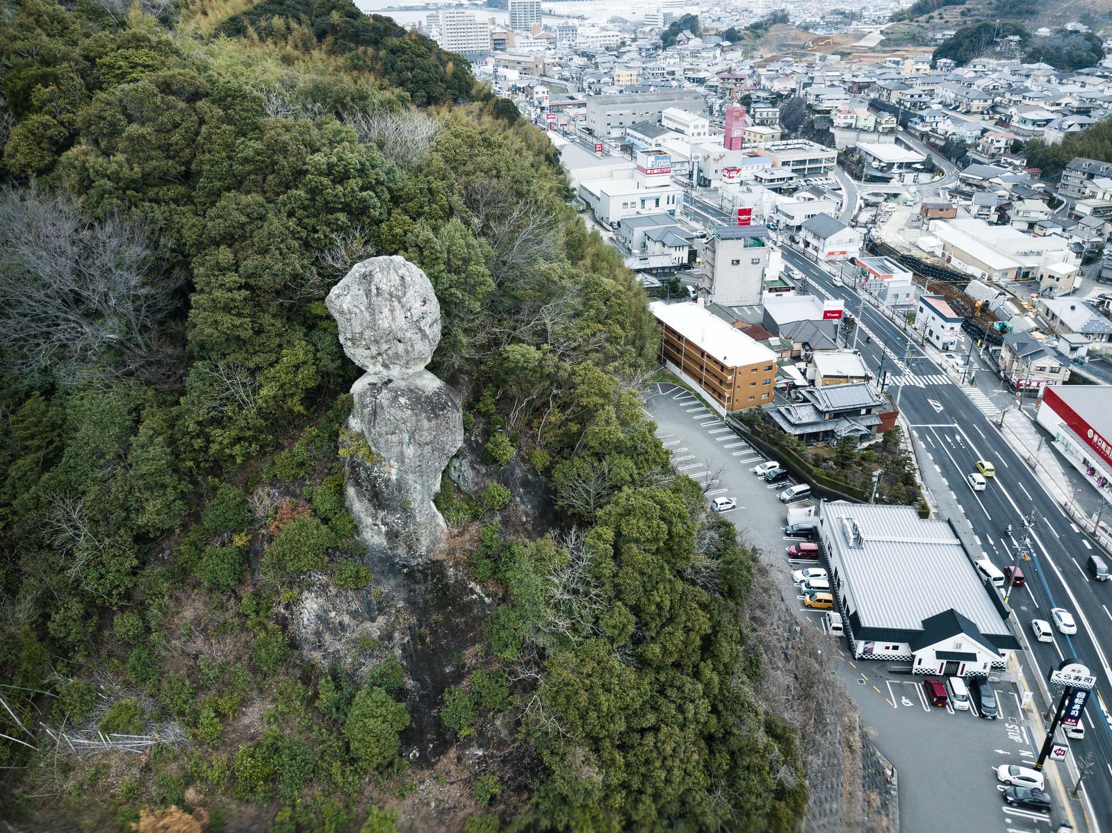 「車通りが多い街中にある落ちそうな巨岩(鯖くさらかし岩)」の写真