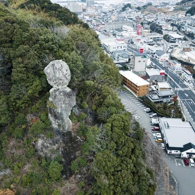車通りが多い街中にある落ちそうな巨岩(鯖くさらかし岩)の写真