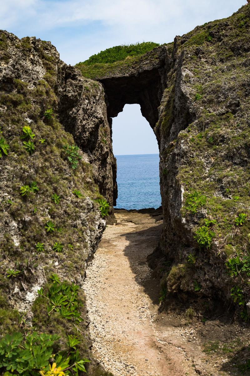 「人畜の犬の群れを捕まえて海に投げた由来がある犬の門蓋のメガネ岩」の写真