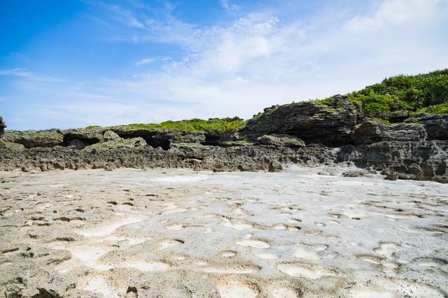 珊瑚の岩のくぼみと塩田跡ミヤドーバル(犬田布海岸)の写真