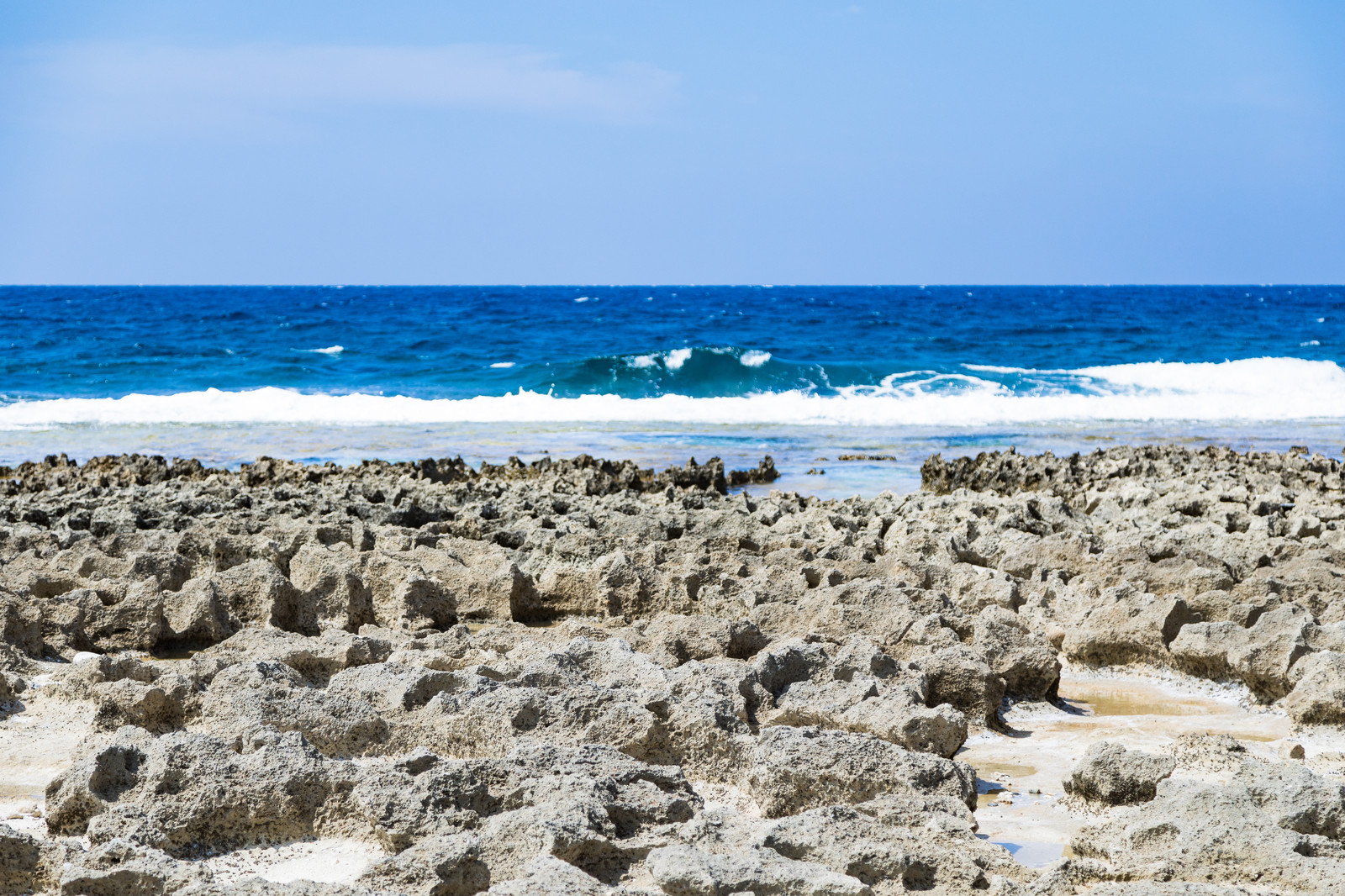 「犬田布海岸のゴツゴツした岩場と海」の写真