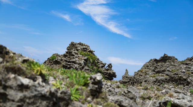 ゴツゴツした岩場と青空の写真