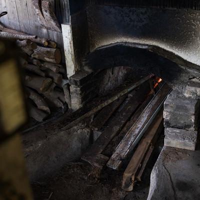 窯を沸騰させる為に蒔を入れる(製塩)の写真