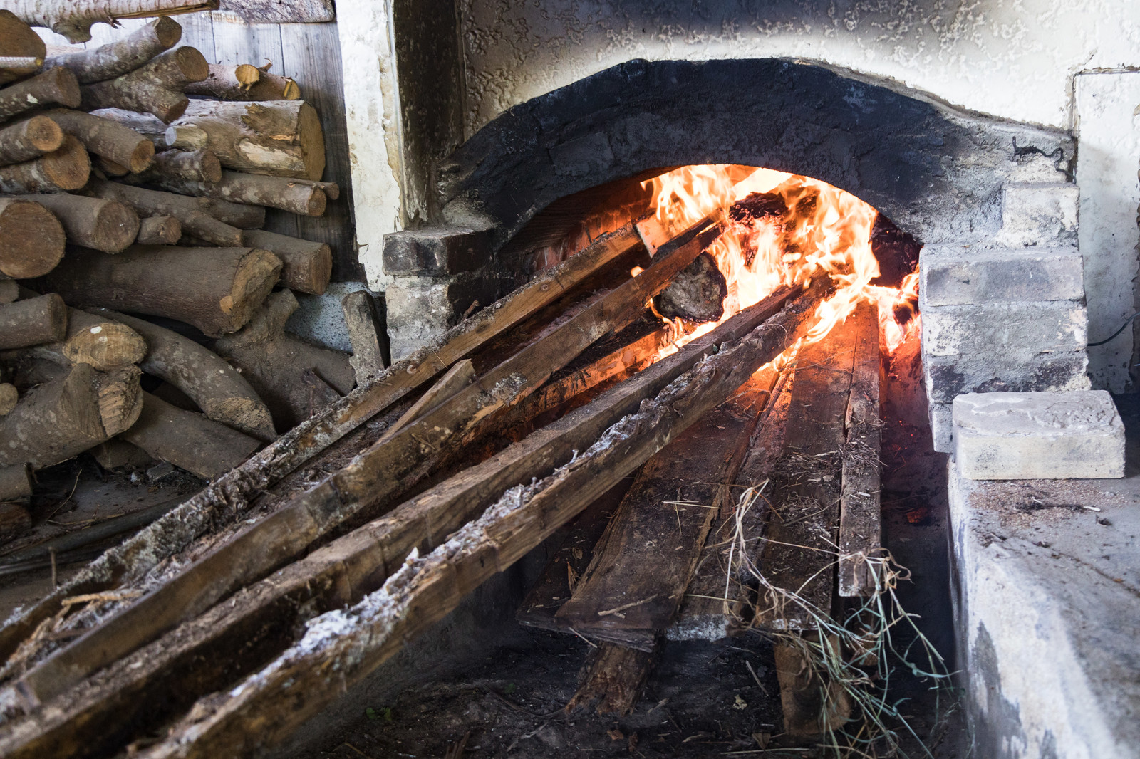 「窯を沸騰させるのに薪を燃やす」の写真