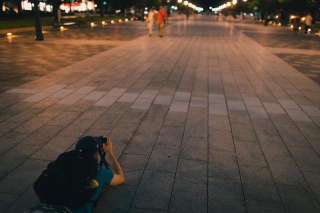 東京駅「丸の内駅前広場」を寝そべり撮影する外国人の写真