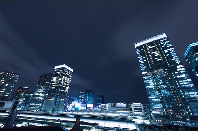 東京駅ホームとビル群(夜景)の写真