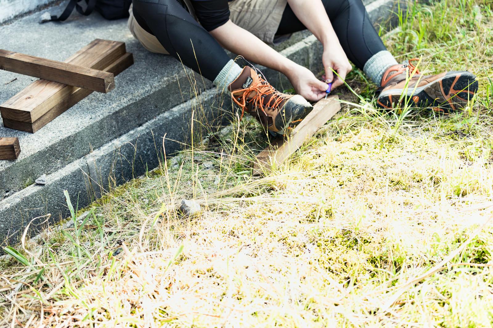 「木の杭に彫刻刀で文字を掘る登山者」の写真