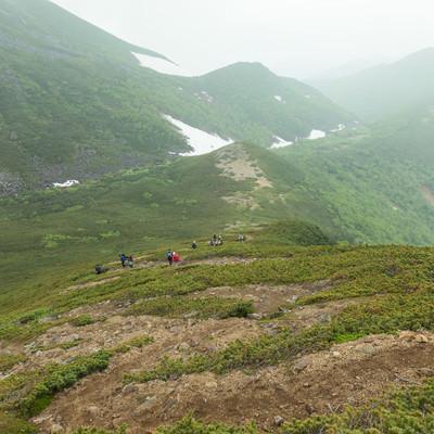 ジグザグの登山道を下山するの写真
