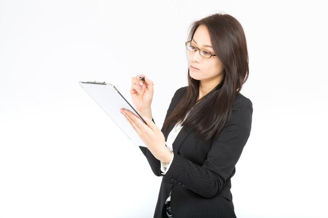 棚卸しをチェックする女性秘書の写真