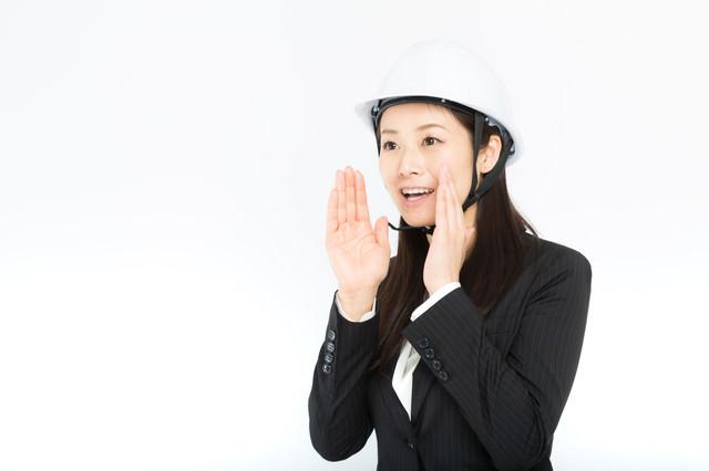 遠方に大声で伝える女性社員の写真