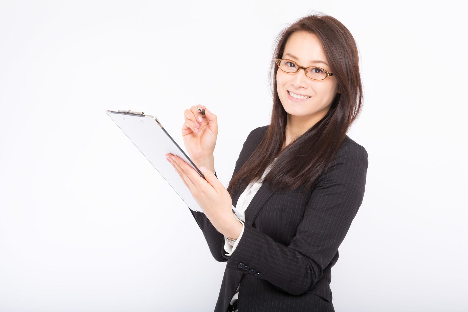 「チェック漏れを笑顔で確認してくる女性社員」の写真[モデル:土本寛子]