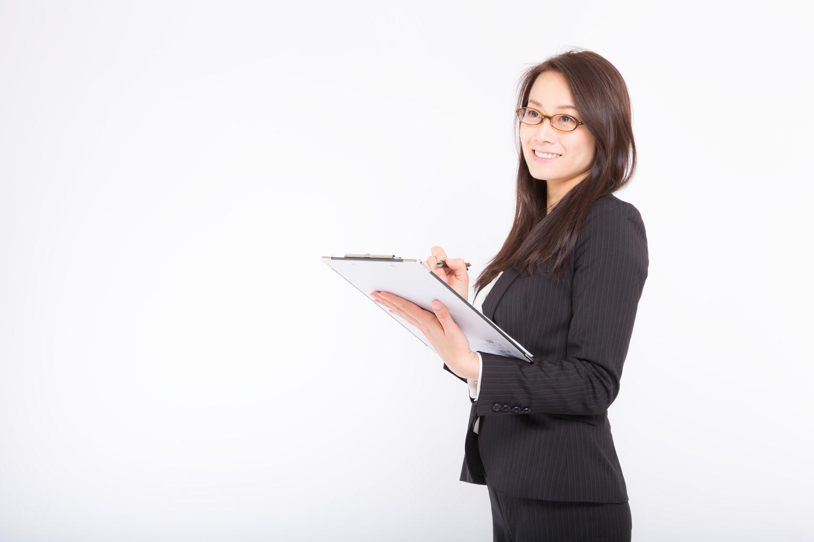 「笑顔で項目にチェックをつける女性」の写真[モデル:土本寛子]