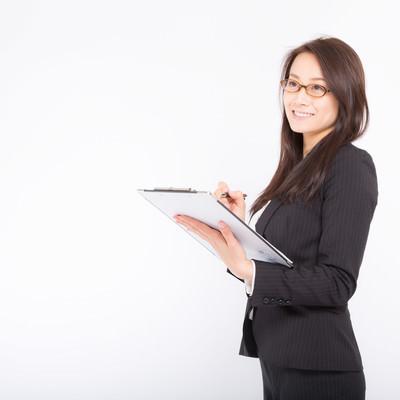 「笑顔で項目にチェックをつける女性」の写真素材