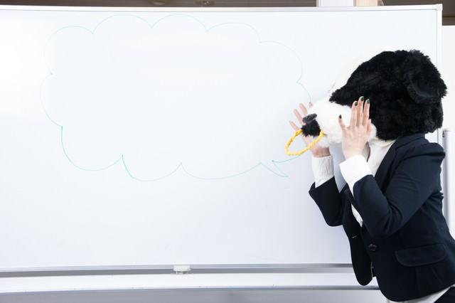 会議室のホワイトボードに吹き出しを書く牛上司の写真