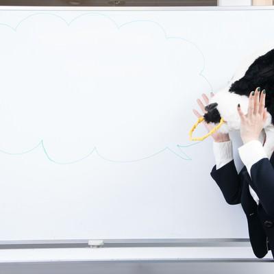 「会議室のホワイトボードに吹き出しを書く牛上司」の写真素材