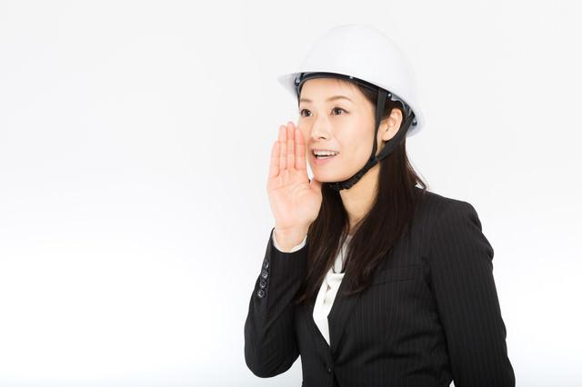 ヘルメットをかぶって声をかける女性社員の写真