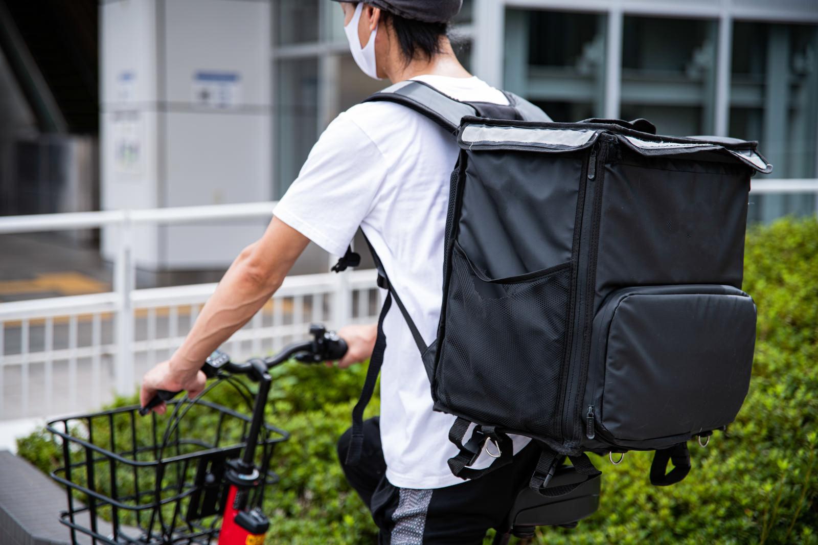 「フードデリバリーの四角いバッグを背負う配達員」の写真