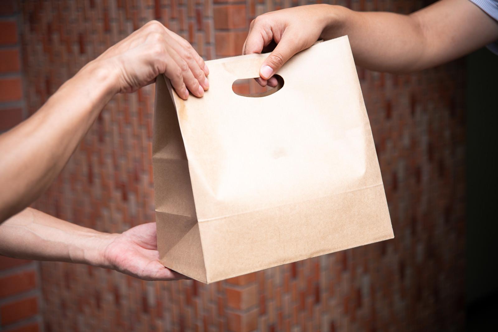 「フードデリバリーの商品受け渡し」の写真