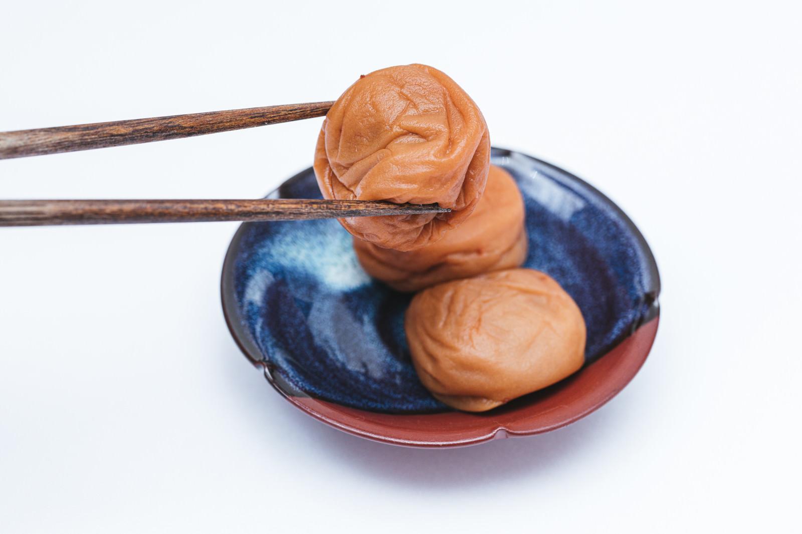 「箸で梅干しを掴む」の写真