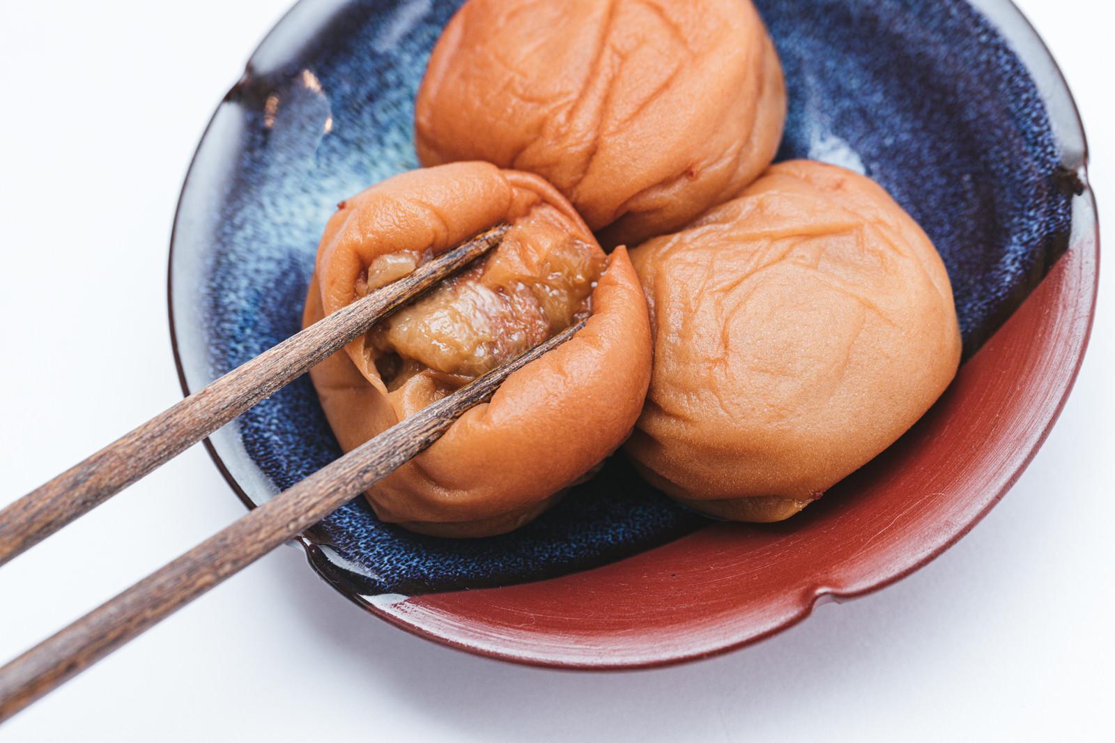 「箸で梅干しの皮を開く」の写真