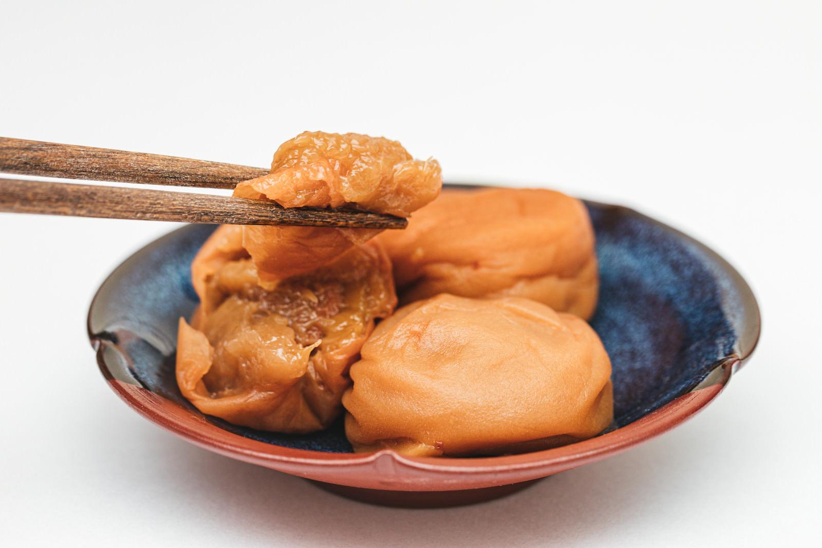 「梅干しの梅肉を箸で掴む」の写真