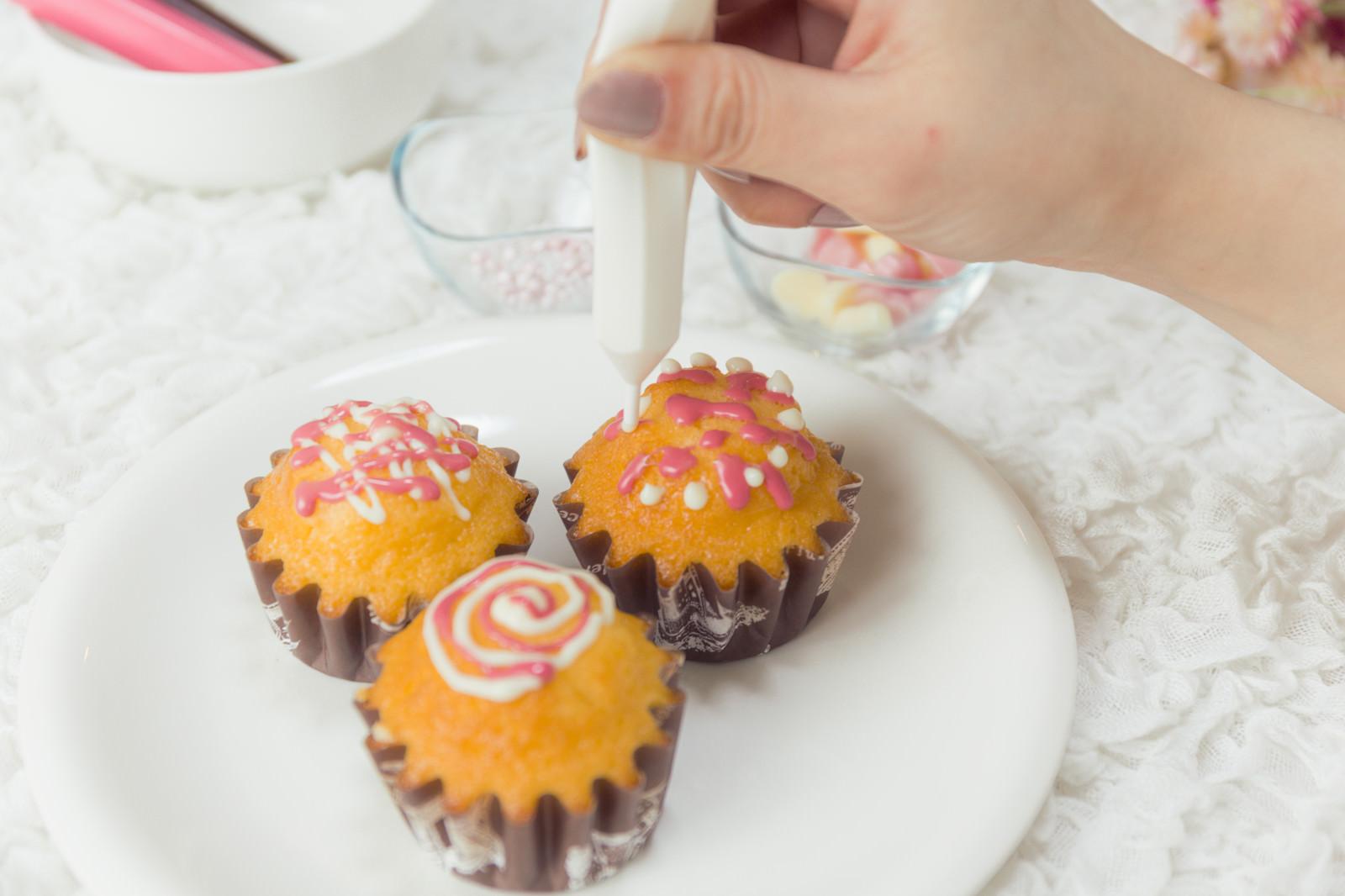 「ホワイトチョコをデコレーション中のカップケーキ」の写真
