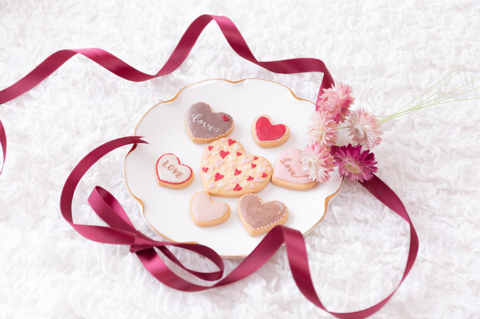 「花を添えて並べたバレンタインクッキー」の写真