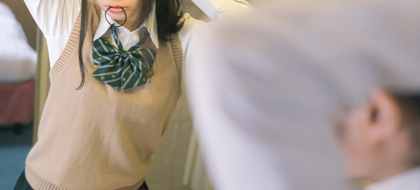 「ヘアゴムを口に咥えて髪をあげる女子高生」の写真[モデル:石投げて美奈代]