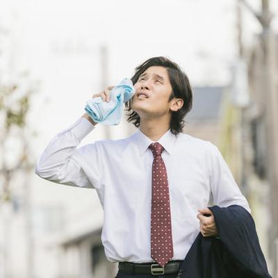 「猛暑の中、飛び込み営業中の新卒男性」の写真素材