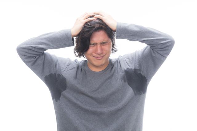 両脇汗かきマン、絶望で頭を抱えるの写真