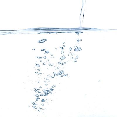 水面と注ぐ水の気泡の写真