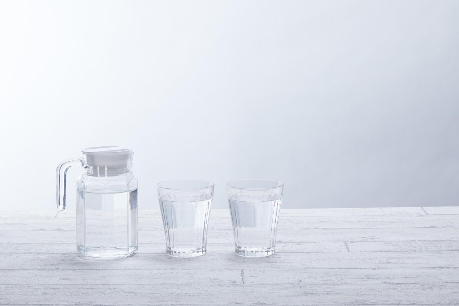 「テーブルに置かれたグラスとミネラルウォーター」の写真